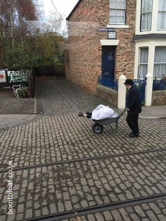 man in bowler hat suit pushing wheelbarow body cobbled street