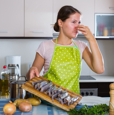 woman kitchen holding nose fish smell